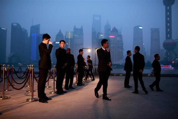 Security guards stand in front of a entrance of the Louis Vuitton fashion show in Shanghai, July 19, 2012.