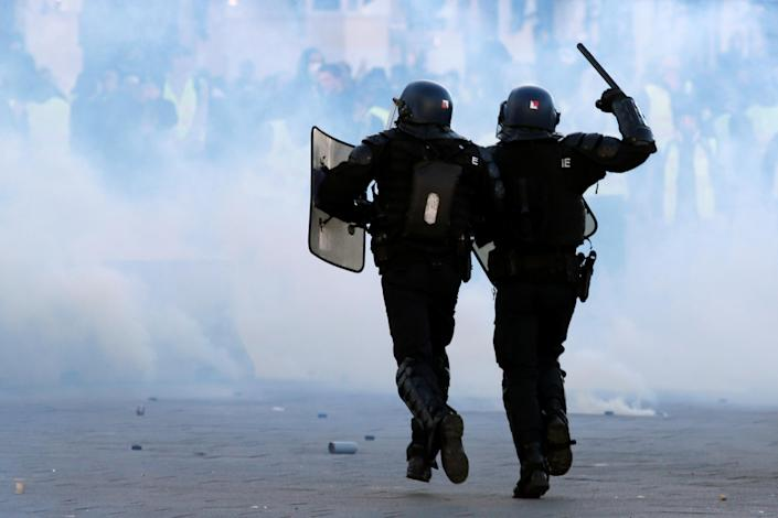"""French Gendarmes run during clashes at a demonstration of the """"yellow vests"""" movement in Marseille, France, Dec. 8, 2018. (Photo: Jean-Paul Pelissier/Reuters)"""
