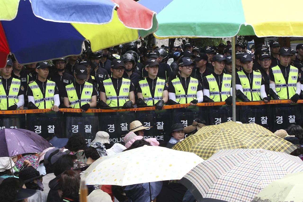 Evangelical Baptist Church believers sit as police officers stand in line in font of the main gate of the church in Anseong, South Korea, Wednesday, June 11, 2014. Thousands of South Korean police officers stormed a church compound Wednesday in their hunt for a fugitive billionaire businessman over April's ferry sinking that left more than 300 people dead or missing, officials said. (AP Photo/Ahn Young-joon)