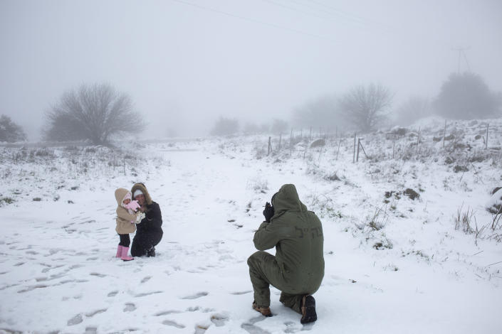 An Israeli reserve solider takes photos of his family in the snow near the Quneitra border crossing between Syria and the Israeli-controlled Golan Heights, Wednesday, Feb. 17, 2021. (AP Photo/Ariel Schalit)