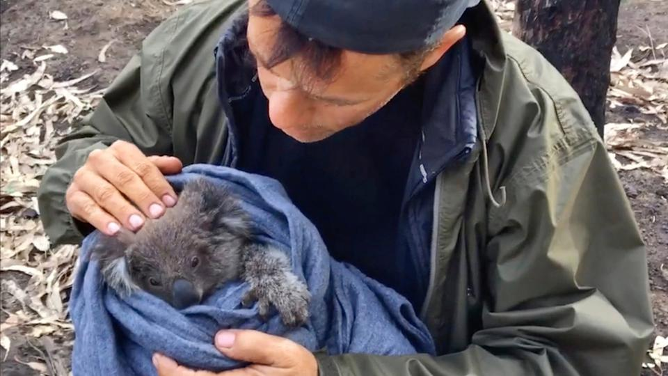 Thron with a koala rescued after the devastating fires in Australia in 2020. (Photo: CuriosityStream)