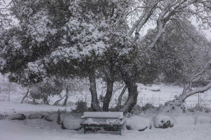 A bench is covered in snow at a memorial site near the Quneitra border crossing between Syria and the Israeli-controlled Golan Heights, Wednesday, Feb. 17, 2021. (AP Photo/Ariel Schalit)
