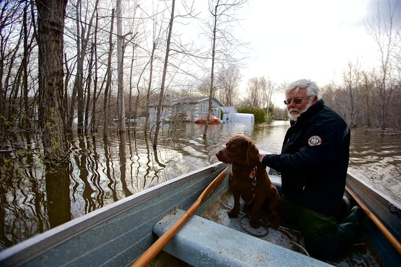 Michel Guerard and his dog Choco return with their boat to help their neighbors to evacuate from their houses affected by floodwaters in Pointe-Calumet, Quebec (The Canadian Press)