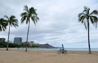 A cyclist rides along an empty Waikiki Beach in Honolulu, Hawaii as Hurricane Douglas veers northward, sparing Oahu from a direct hit