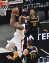 Los Angeles Clippers center Serge Ibaka (9) shoots as Memphis Grizzlies guard Ja Morant (12) gets a hand in front of his face during the first half of an NBA basketball game Friday, Feb. 26, 2021, in Memphis, Tenn. (AP Photo/Brandon Dill)