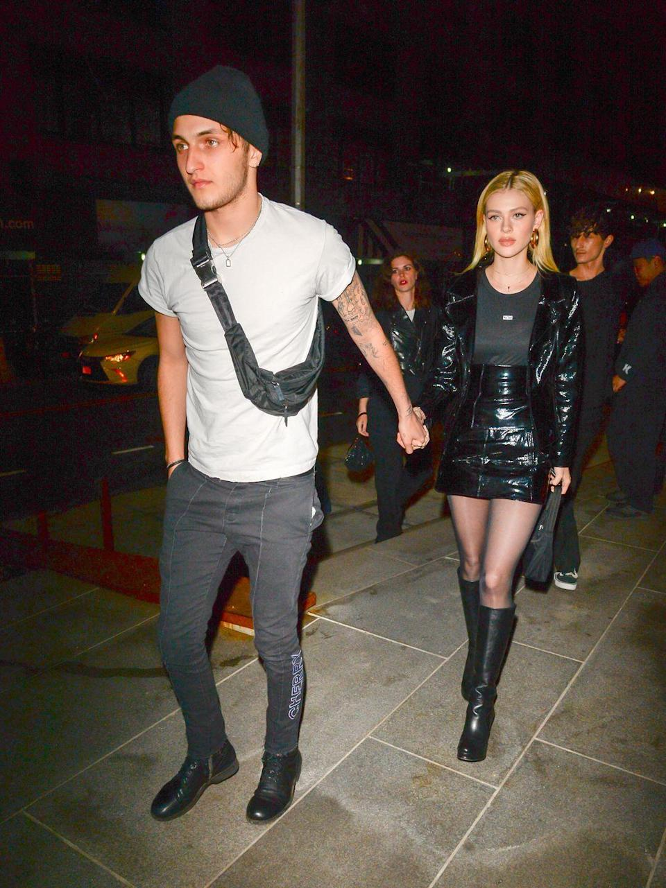 <p>To celebrate then-boyfriend Anwar Hadid's sister's birthday party in NYC, Peltz wore a pair of black knee-high leather shoes, a black high-waisted skirt, a black leather jacket and grey T-shirt. </p>