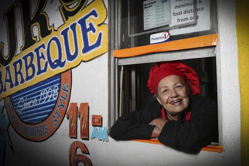 Jeanie Jackson, founder of JR's Barbecue, leans out of the take-out window in a red chef's hat.