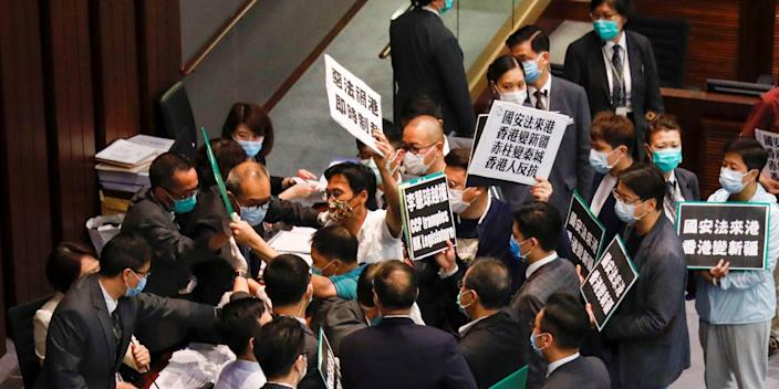 Democratic legislators in Hong Kong scuffle with security as they protest against new security laws at a Legislative Council committee meeting on May 22, 2020.