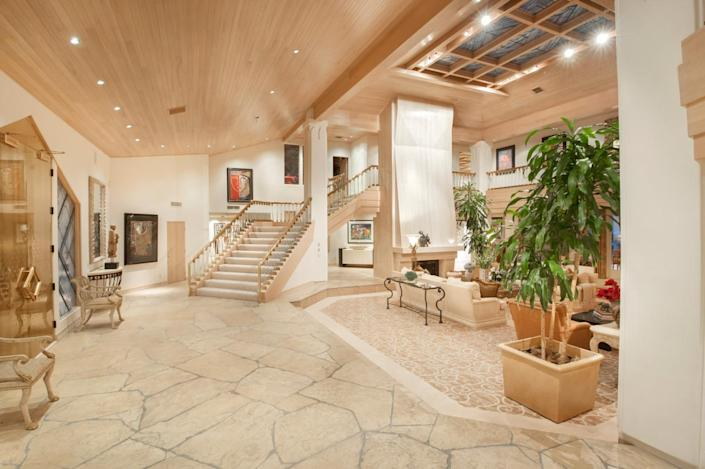 """<p>The gold-clad front doors are at left in this photo. (All photos via <a href=""""http://bit.ly/1OjQdjg"""" rel=""""nofollow noopener"""" target=""""_blank"""" data-ylk=""""slk:Concierge Auctions listing"""" class=""""link rapid-noclick-resp"""">Concierge Auctions listing</a>)<br></p>"""