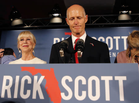 Republican U.S. Senate candidate Rick Scott pauses as he addresses supporters while accompanied by his wife Ann (L) at his midterm election night party in Naples, Florida, U.S. November 6, 2018. REUTERS/Joe Skipper