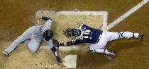 Milwaukee Brewers catcher Yasmani Grandal tags out Milwaukee Brewers' Christian Yelich at home during the seventh inning of a baseball game Tuesday, June 25, 2019, in Milwaukee. (AP Photo/Morry Gash)