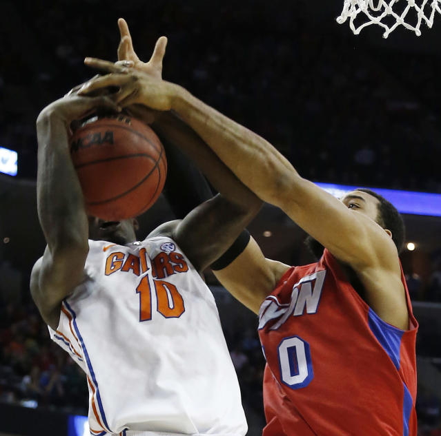 Florida forward Dorian Finney-Smith (10) and Dayton forward/center Devon Scott (40) work for a rebound during the first half in a regional final game at the NCAA college basketball tournament, Saturday, March 29, 2014, in Memphis, Tenn. (AP Photo/Mark Humphrey)