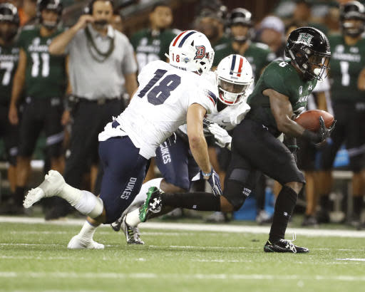 Hawaii wide receiver Cedric Byrd (6) runs through Duquesne linebacker Brett Zanotto (18) and defensive back Greg Claytor Jr. (22) during the second quarter of an NCAA college football game Saturday, Sept. 22, 2018, in Honolulu. (AP Photo/Marco Garcia)