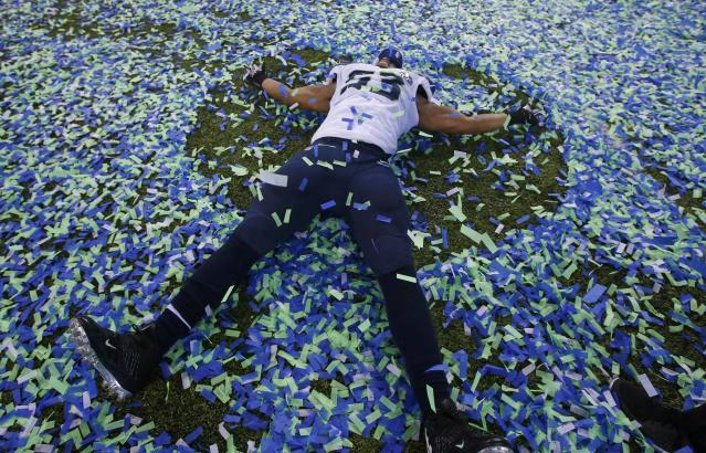 Seattle Seahawks Malcom Smith makes an angel in the confetti after his team defeated the Denver Bronocs in the NFL Super Bowl XLVIII football game in East Rutherford, New Jersey, February 2, 2014. REUTERS/Shannon Stapleton (UNITED STATES - Tags: SPORT FOOTBALL)