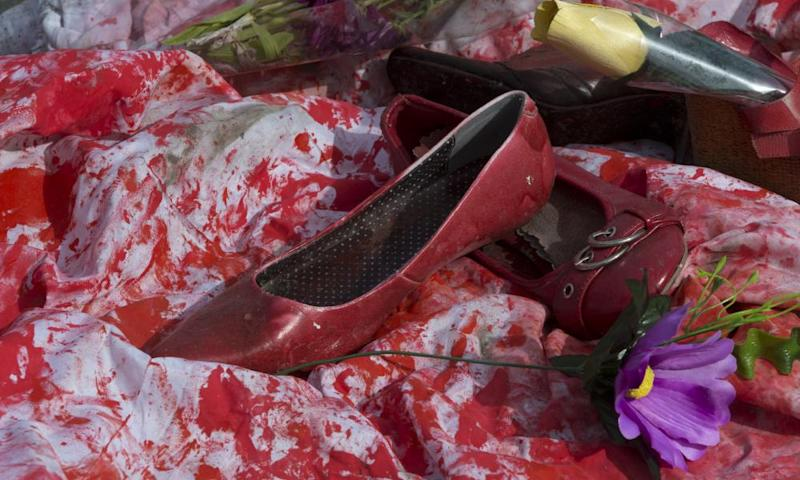 Red shoes and flowers placed by members of a women's group to promote International Women's Day in Puerta del Sol square in Madrid, Spain.