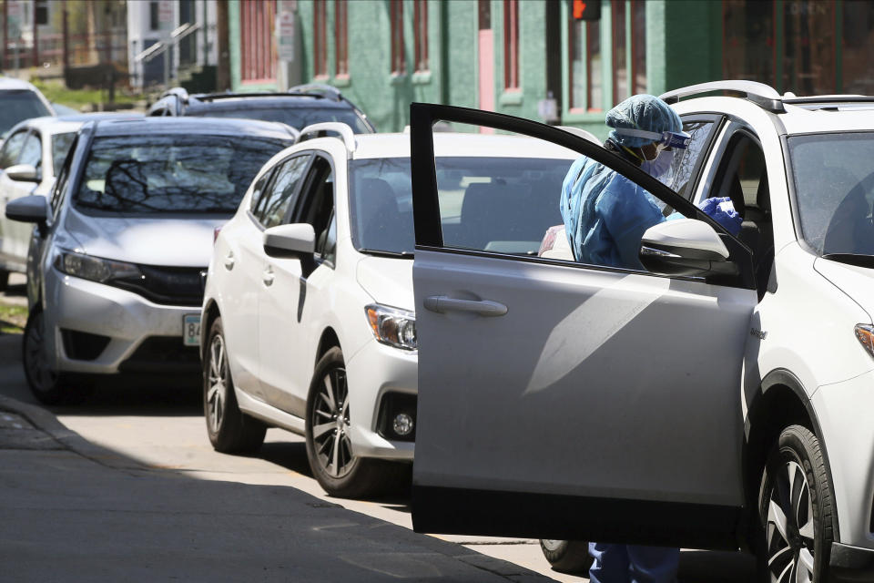 A health worker does a drive-up test on a driver at People's Center, Monday, April 27, 2020, in Minneapolis during expanded coronavirus testing as Minnesota Gov. Tim Walz tries to get the numbers of tests up. (AP Photo/Jim Mone)