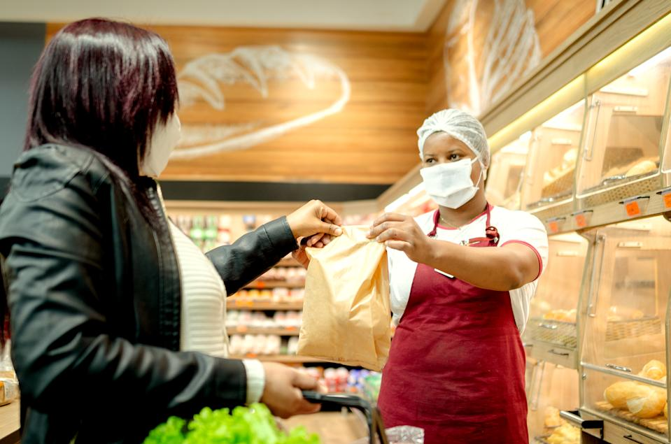 Woman at a bakery serving a customer