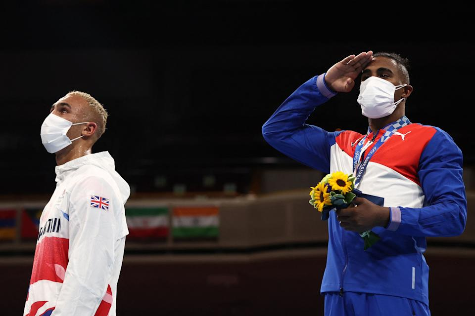 Gold medallist Cuba's Arlen Lopez (R) celebrates on the podium next to silver medallist Britain's Benjamin Whittaker after their men's light heavy (75-81kg) boxing final bout during the Tokyo 2020 Olympic Games at the Kokugikan Arena in Tokyo on August 4, 2021. (Photo by Buda Mendes / POOL / AFP) (Photo by BUDA MENDES/POOL/AFP via Getty Images)