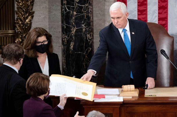 PHOTO: Vice President Mike Pence hands the electoral certificate from the state of Arizona to Sen. Amy Klobuchar, as he presides over a joint session of Congress to certify the 2020 election results on Capitol Hill  Jan. 6, 2021.  (Pool/Saul Loeb/Pool via Reuters)