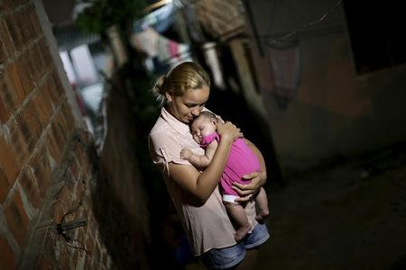 Gleyse Kelly da Silva embraces her daughter Maria Giovanna, who has microcephaly, in Recife, Brazil, January 25, 2016. REUTERS/Ueslei Marcelino/Files
