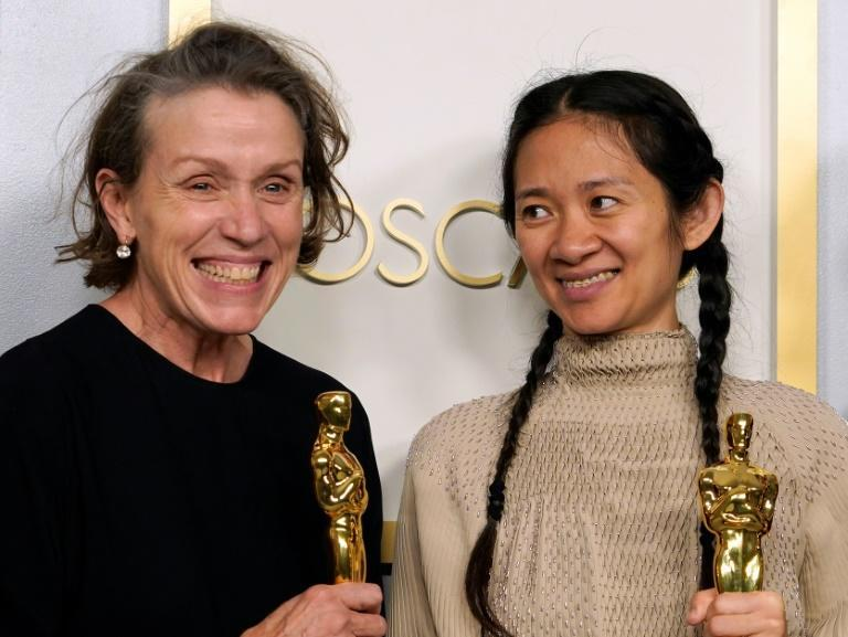 """Frances McDormand (L) won the Oscar for best actress in """"Nomadland"""" -- her third acting win -- but also shared the film's award for best picture as one of its producers with director Chloe Zhao (R)"""