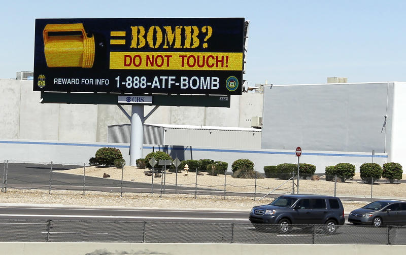 One of twenty public service announcement billboards on display across the Phoenix metro area along highways are warning citizens about picking up discarded flashlights Thursday, June 7, 2012, in Phoenix. In three separate incidents, unsuspecting bystanders picked up standard-looking yellow flashlights and flicked the switch to turn them on. But instead of lighting up as they should have, bombs that had been left inside the flashlights exploded in their hands. Five people in all received minor injuries, but authorities in the Phoenix area still have no idea who committed the bombings last month.(AP Photo/Ross D. Franklin)