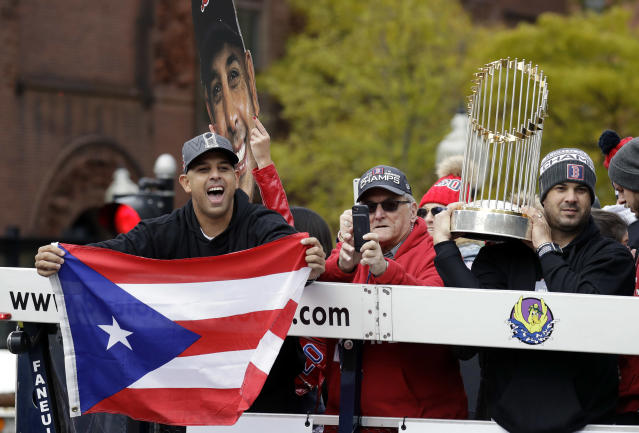 "<a class=""link rapid-noclick-resp"" href=""/mlb/teams/bos"" data-ylk=""slk:Boston Red Sox"">Boston Red Sox</a> manager Alex Cora waves the flag of Puerto Rico as coach Ramon Vazquez holds the championship trophy during the World Series parade. (AP)"