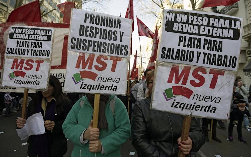 "Demonstrators hold signs reading ""Not a peso for the debt. Money for salary and work"" as they march from Plaza de Mayo to the Congress building in Buenos Aires on August 27, 2014 (AFP Photo/Juan Mabromata)"