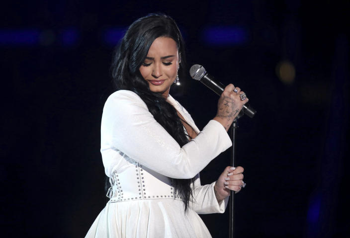 """FILE - Demi Lovato performs """"Anyone"""" at the 62nd annual Grammy Awards on Jan. 26, 2020, in Los Angeles. Lovato reveals publicly for the first time details about her near-fatal drug overdose in 2018 in """"Demi Lovato: Dancing With the Devil,"""" a four-part docuseries debuting March 23, 2021, on YouTube Originals. (Photo by Matt Sayles/Invision/AP, File)"""