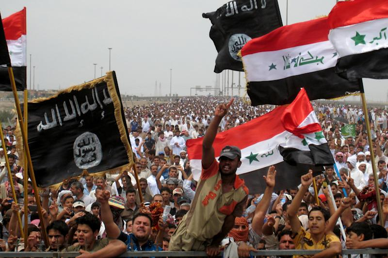 FILE -- Sunni protesters wave Islamist flags while others chant slogans at an anti-government rally in Fallujah, Iraq, Friday, May 3, 2013. The leader of al-Qaida's Iraq arm, Abu Bakr al-Baghdadi, defiantly rejected an order from the terror network's global command to scrap a merger with the organization's Syria affiliate, according to a message purporting to be from Al-Baghdadi that was posted online Saturday, June 15, 2013. (AP Photo/Bilal Fawzi, File)