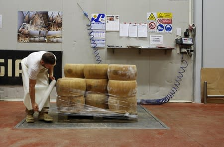 FILE PHOTO: A woorker packages wheel of Parmesan cheese at storehouse shelf 4 Madonne Caseificio dell'Emilia dairy cooperative in Modena