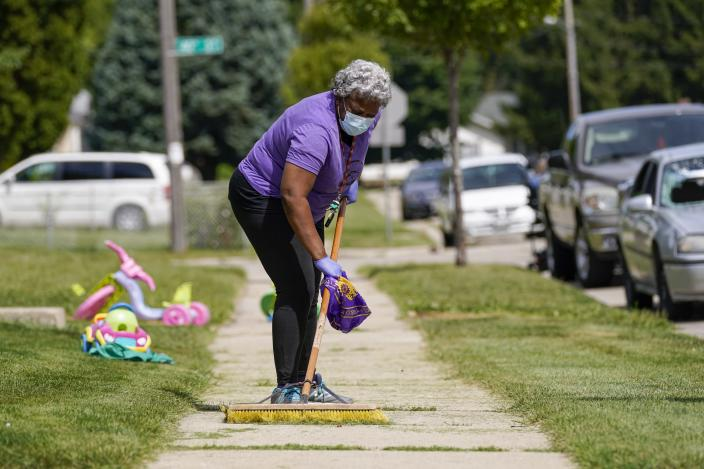 Church volunteer Patricia Antoine-Norton helps clean up the neighborhood where Jacob Blake was shot last Sunday on Saturday, Aug. 29, 2020, in Kenosha, Wis. Family members of Jacob Blake, a Black man who was paralyzed after a Kenosha police officer shot him in the back, are leading a march and rally Saturday to call for an end to police violence. (AP Photo/Morry Gash)