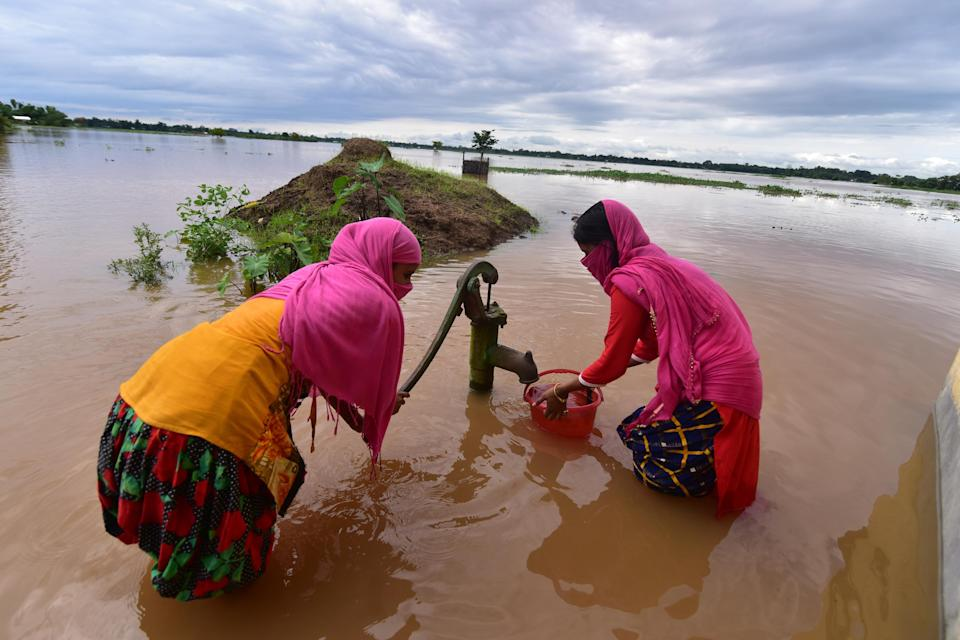 NAGAON,INDIA-JULY 22,2020 : Girls fetches water from a partially submerged hand pump at Madhabpara village in Nagaon district, in the northeastern state of Assam, India- PHOTOGRAPH BY Anuwar Ali Hazarika / Barcroft Studios / Future Publishing (Photo credit should read Anuwar Ali Hazarika/Barcroft Media via Getty Images)