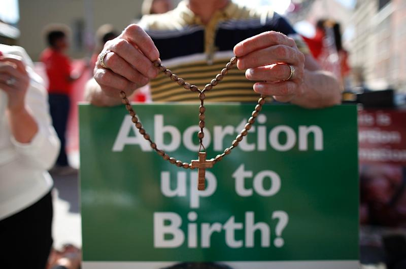 A protester holds rosary beads and an anti-abortion placard in front of the gates of the Irish Parliament (AFP Photo/PETER MUHLY)