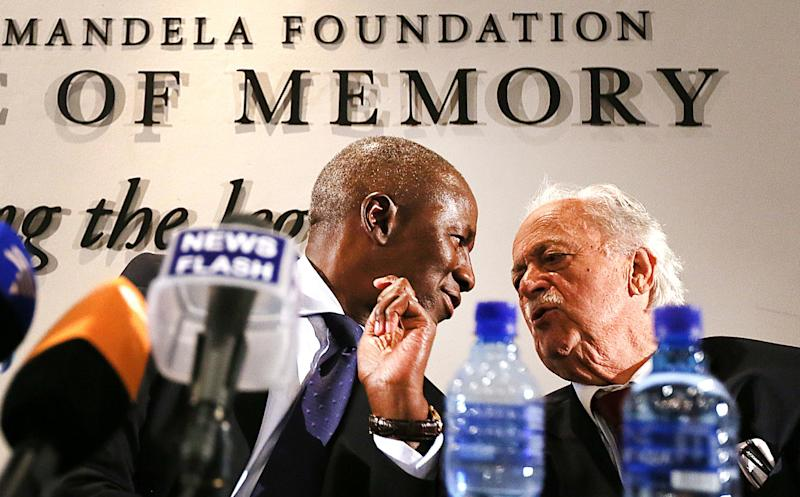 South Africa's deputy chief justice Dikgang Moseneke, left, chats with Advocate George Bizos, right, during their media briefing after a will was read in its entirety to members of Mandela's family at the Nelson Mandela Foundation in Johannesburg, South Africa, Feb. 3, 2014. The Nelson Mandela Foundation Nelson Mandela's estate is worth roughly $4.1 million, excluding royalties and other amounts, and beneficiaries of his will include his family, members of his staff, schools that he attended and the African National Congress, the movement that fought white rule and now governs South Africa, the will's executors said Monday. (AP Photo/STR)