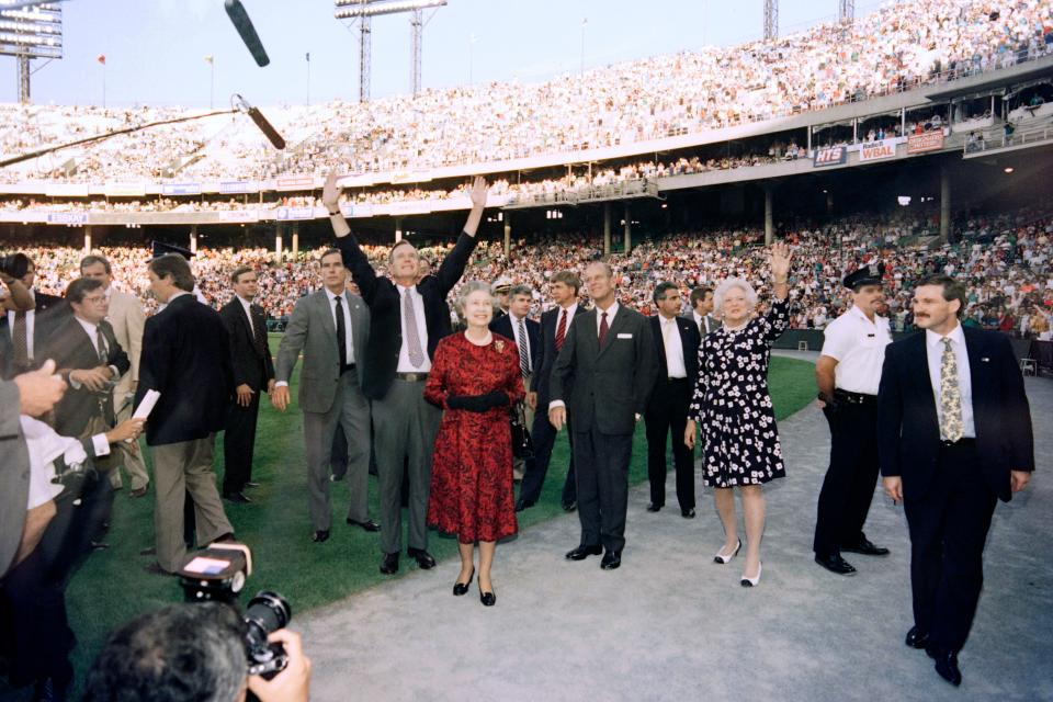 The Queen and Prince Philip wave to the crowd with President George Bush and First Lady Barbara ahead of a baseball game between the Orioles and the Oakland Athletics at the Memorial Stadium in Baltimore. (J. DAVID AKE/AFP via Getty Images)