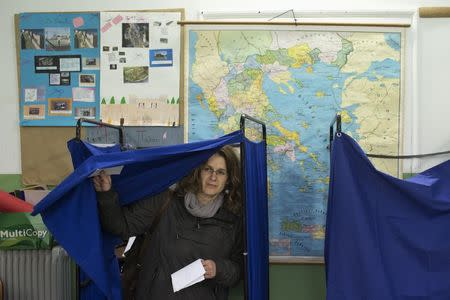 A woman exits a voting booth to cast her ballot at a polling station in an elementary school during Greece's parliamentary elections in Athens January 25, 2015. REUTERS/Marko Djurica