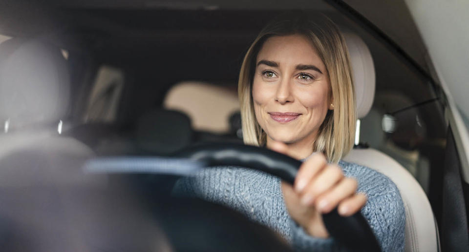 Portrait of smiling young woman driving a car. Source: Getty Images