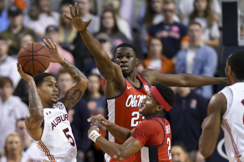 Mississippi forward Sammy Hunter (23) and guard Devontae Shuler (2) defend against Auburn guard J'Von McCormick (5) during the first half of an NCAA college basketball game Tuesday, Feb. 25, 2020, in Auburn, Ala. (AP Photo/Julie Bennett)