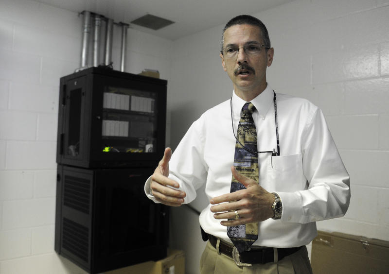Senior Warden Michael Roesler explains a cell phone blocking system, left, at the Stiles Unit of the Texas Department of Criminal Justice system Wednesday, March 13, 2013, in Beaumont, Texas. The new technology is being installed at the prison to divert calls, texts, emails and internet log-in attempts from contraband phones. (AP Photo/Pat Sullivan)