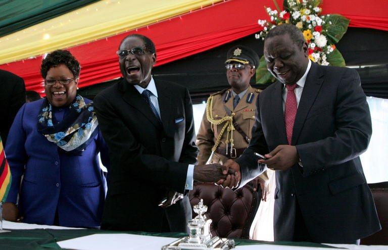 Zimbabwe's President Robert Mugabe (C) laughs as he shakes hands with Prime Minister Morgan Tsvangirai (R) and Vice President Joice Mujuru (L) after signing Zimbabwe's new constitution at the State House in Harare on May 22, 2013