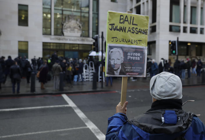 """A Julian Assange supporter holds up a placard outside Westminster Magistrates Court as his bail hearing is held at the court in London, Wednesday, Jan. 6, 2021. On Monday Judge Vanessa Baraitser ruled that Julian Assange cannot be extradited to the US. because of concerns about his mental health. Assange had been charged under the US's 1917 Espionage Act for """"unlawfully obtaining and disclosing classified documents related to the national defence"""". Assange remains in custody, the US. has 14 days to appeal against the ruling.(AP Photo/Matt Dunham)"""