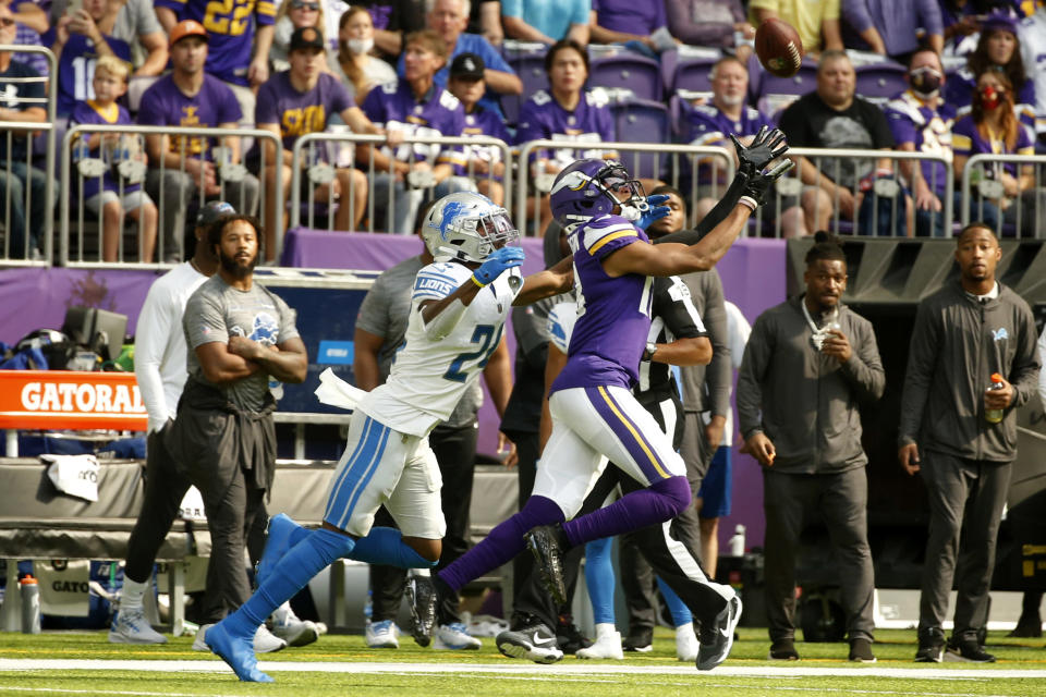 Minnesota Vikings wide receiver Justin Jefferson (18) catches a pass ahead of Detroit Lions cornerback Amani Oruwariye (24) during the first half of an NFL football game, Sunday, Oct. 10, 2021, in Minneapolis. (AP Photo/Bruce Kluckhohn)