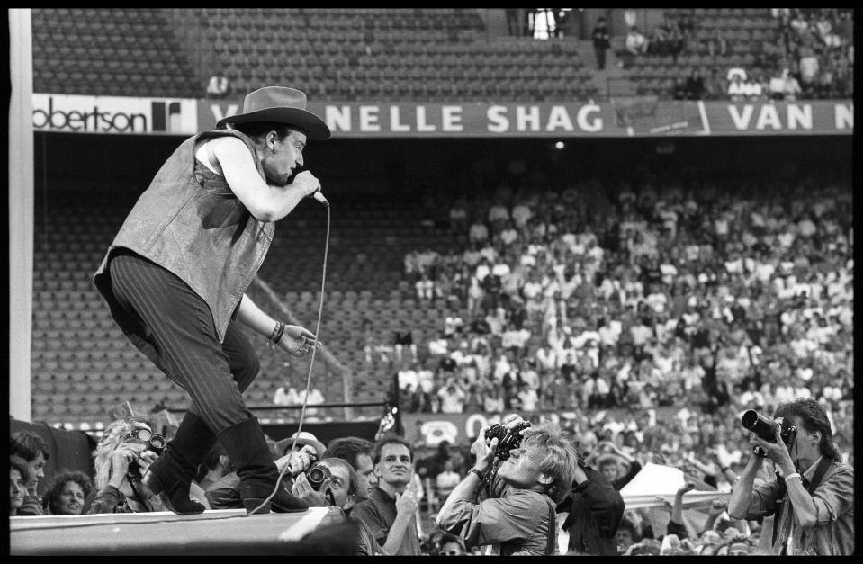 Bono of U2 performs to photographers at the front of the stage on The Joshua Tree Tour at Feyenoord Stadion, De Kuip, Rotterdam ,Netherlands, 10th July 1987. The three photographers shooting are from left to right: Barton van Vlijmen, Rolf Bos, Paul Bergen. (Photo by Rob Verhorst/Redferns)