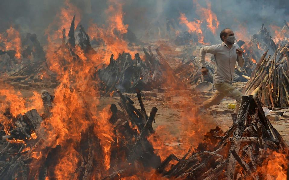 A man runs to escape heat emitting from the multiple funeral pyres of Covid-19 victims at a crematorium on the outskirts of New Delhi, India - Amit Sharma/AP