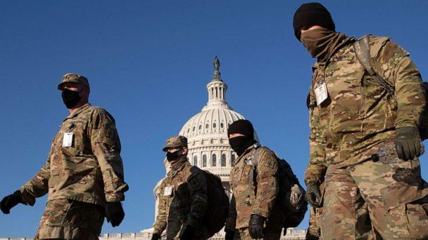 PHOTO: Members of the National Guard walk on the grounds of the East Front of the U.S. Capitol in Washington, D.C, Jan. 12, 2021. (Michael Reynolds/EPA via Shutterstock)