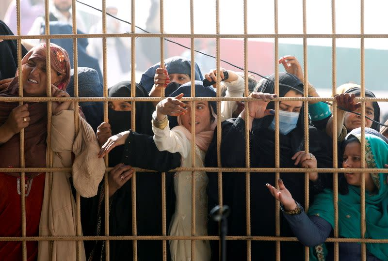 Afghan women wait to receive tokens needed to apply for the Pakistan visa, after some people were killed in a stampede in Jalalabad