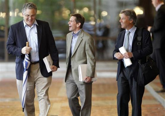 Investors holding literature explaining the Facebook stock share a laugh as they leave the Four Season's Hotel after attending a show for Facebook''s initial public offering in Boston, May 8, 2012.