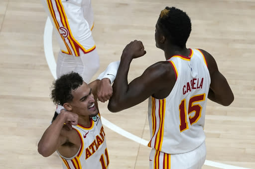 Atlanta Hawks guard Trae Young (11) and center Clint Capela (15) celebrate a basket in overtime of the team's 123-115 victory over the Detroit Pistons in an NBA basketball game Wednesday, Jan. 20, 2021, in Atlanta. (AP Photo/John Bazemore)