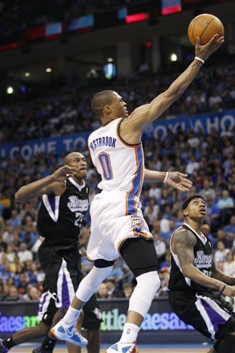 Oklahoma City Thunder guard Russell Westbrook (0) shoots between Sacramento Kings forward Travis Outlaw, left, and guard Isaiah Thomas during the second quarter of an NBA basketball game in Oklahoma City, Tuesday, April 24, 2012. (AP Photo/Sue Ogrocki)